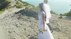 Bride and groom walking along the coastal cliffs Stock Footage