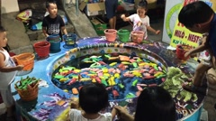 Children catch toy fish while their parents watch dogs race Stock Footage