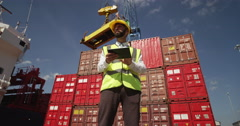 A customs inspector standing and reviewing a tack of containers. - stock footage