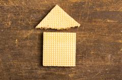 Simple house design illustrated by using rectangular and a triangular cookie on - stock photo