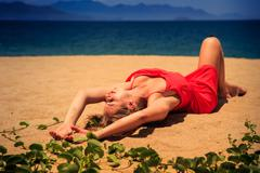 upper view blond girl in red frock lies on sand bends knee - stock photo