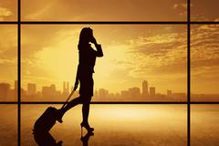 Silhouette of business woman walking with suitcase Stock Photos