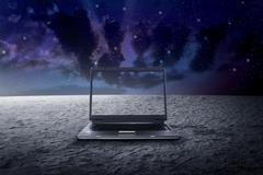 Big laptop on the outer space - stock photo