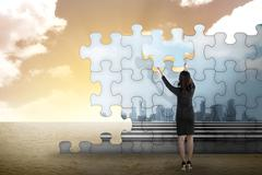 Business person building puzzle of city in the desert - stock photo