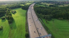Aerial footage of traffic and green fields surrounding Stock Footage