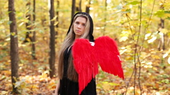 Beautiful girl with red angel wings in forest Stock Footage