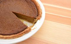 Close-up of cut pumpkin pie with slice taken - stock photo