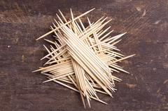 Many toothpicks tightly piled together facing different directions on dark - stock photo