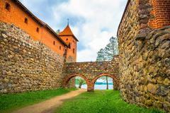 Old castle walls, archs and tower - stock photo