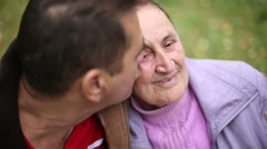 Family values: Seniors mother and son in autumn park, son kissing his mother - stock footage