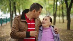 Family values: Seniors mother and son walking in autumn park - stock footage