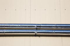 Metal chrome pipes on siding wall - stock photo