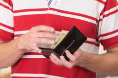 Man wearing red white striped shirt holding wallet with money and cards visible Stock Photos