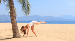 Blonde girl in lace makes hand stand pose to palm on beach Stock Footage