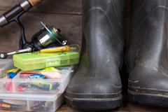 Fishing tackles and rubber boots on timber board Stock Photos