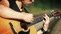A portrait of a young guitarist performing song played in chords Stock Footage