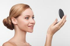 Attractive young woman is checking her appearance - stock photo