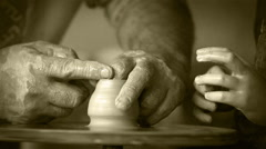 Aged craftsman's hands creating a piece of pottery teaching his little student Stock Footage