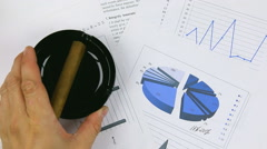 Stock Video Footage of Businessman  puts an  black ashtray and cigar on chart, a top view