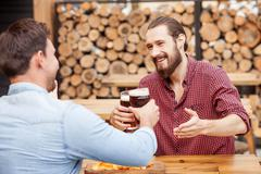 Stock Photo of Cheerful young men are resting in pub