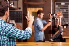 Attractive young guy orders lager in pub Stock Photos