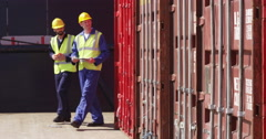 An African American woman discussing logistics with a manager at a shipyard. Stock Footage