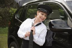 Attractive woman chauffeur tying her uniform tie in the wing mirror of her ca Kuvituskuvat