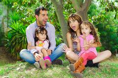 Beautiful hispanic family of four sitting outside on grass engaging in Stock Photos