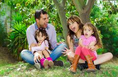 Beautiful hispanic family of four sitting outside on grass engaging in - stock photo