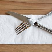 Fork and Knife Cutlery on white tissue - stock photo