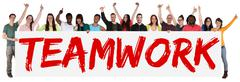 Teamwork team group of young multi ethnic people holding banner - stock photo