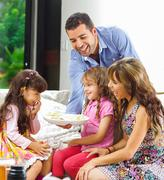 Hispanic parents with two daughters eating from a tray of potato chips sitting Stock Photos
