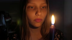 Teen girl with a candle, fear on her face - stock footage