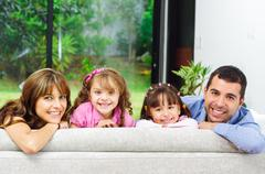Beautiful hispanic family of four posing with heads sticking up from back sofa - stock photo