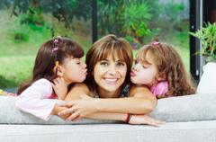 Beautiful hispanic family of four posing with heads sticking up from back sofa Stock Photos