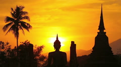 Sunset silhouette of the ancient ruins and Buddha statue, Sukhothai, Thailand Stock Footage