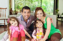 Beautiful hispanic family of four sitting on floor in livingroom posing happily Stock Photos