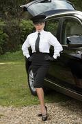 Woman chauffeur in uniform standing alongside her car Stock Photos