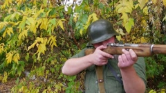 World War II soldiers firing a rifle from the shelter. - stock footage
