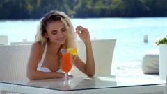 Girl in summer cafe drink orange cocktail Stock Footage