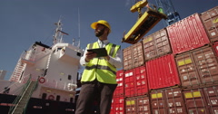 A customs inspector standing and reviewing a tack of containers. Stock Footage