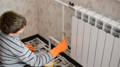 Boy paints a heating radiator in  apartment Stock Footage