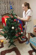 Mom and son decorate the Christmas tree - stock photo