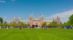 People walk and rest on the Muzeumpleine in Amsterdam in a spring day Stock Footage
