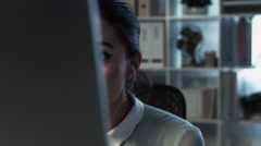 Woman using computer video messaging late at night home office Stock Footage