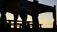 Silhouette boy running around the porch at sunset in nature Stock Footage
