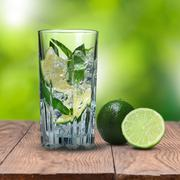 mohito cocktail on wooden table against green background - stock photo