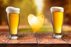 Love beer. Beer in glass with heart splash on wooden table again Stock Photos
