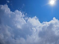 Dark clouds, blue sky and bright sun - stock photo