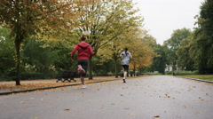 Group of runners running in park wearing wearable technology connected devices Stock Footage